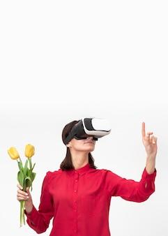 Kobieta z zestawem słuchawkowym wirtualnej rzeczywistości, trzymając kwiaty