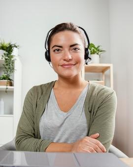 Kobieta z zestawem słuchawkowym za pomocą laptopa