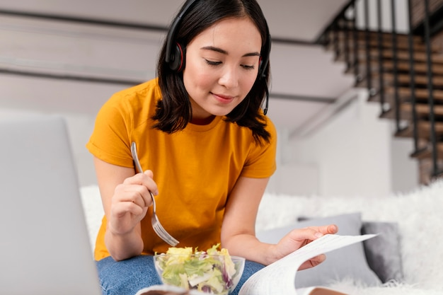 Kobieta z zestawu słuchawkowego jedzenie podczas rozmowy wideo