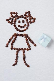Kobieta z ziaren kawy i niebieskie pudełko. prezent kawowy od dziewczyny. na białym tle.