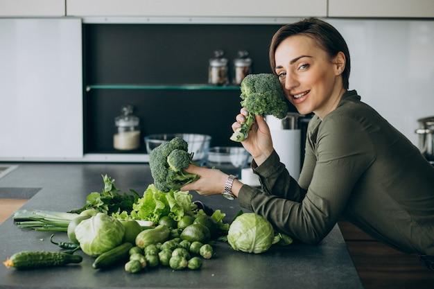Kobieta z zielonymi warzywami w kuchni