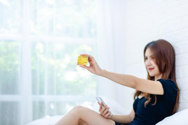 Kobieta z żółtą kartą kredytową w ręku uśmiecha się radośnie