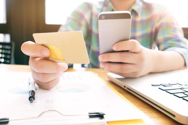 Kobieta za pomoc? laptopa i telefonu komórkowego do zakupów w internecie i p? ac? kart? kredytow ?.