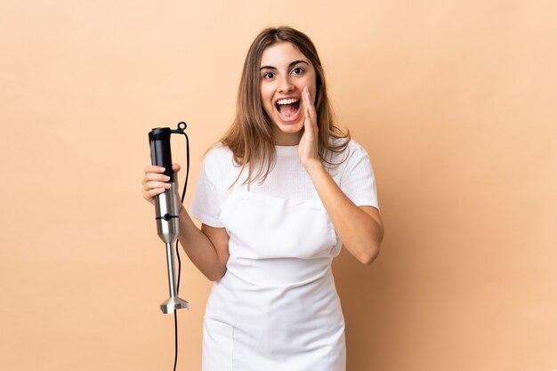 Kobieta za pomocą blendera ręcznego z zaskoczeniem i zszokowanym wyrazem twarzy