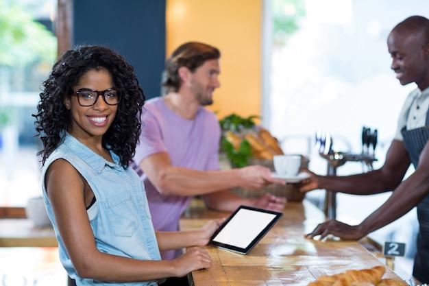 Kobieta za pomocą cyfrowego tabletu, podczas gdy kelner serwuje kawę do człowieka w counterwoman za pomocą cyfrowego tabletu w