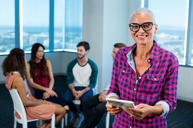 Kobieta za pomocą cyfrowego tabletu, podczas gdy zespół kreatywny biznes za w biurze