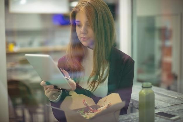 Kobieta za pomocą cyfrowego tabletu podczas jedzenia sałatki