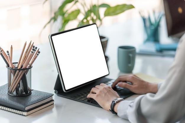 Kobieta za pomocą cyfrowego tabletu, pracując w domu. pusty biały ekran.