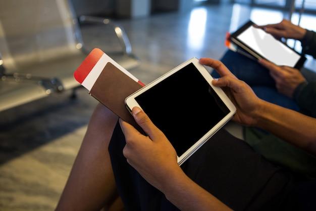 Kobieta za pomocą cyfrowego tabletu w poczekalni na lotnisku