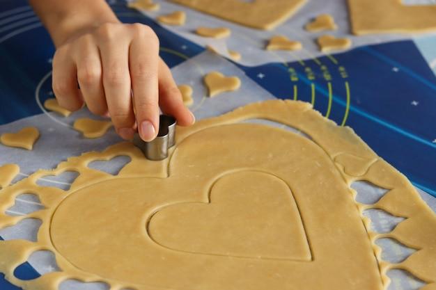 Kobieta za pomocą formy tnie serca na ciasteczka z ciasta