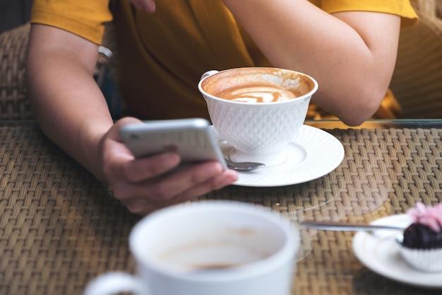 Kobieta za pomocą i patrząc na inteligentny telefon z filiżanki kawy w kawiarni