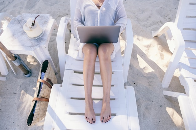 Kobieta za pomocą i wpisując na komputerze przenośnym z pustym ekranem, kładąc się na leżaku na plaży