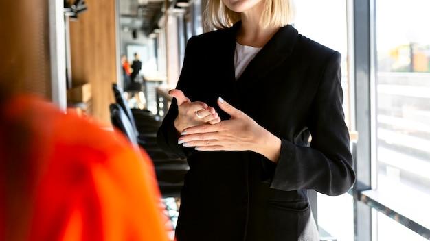 Kobieta za pomocą języka migowego w pracy