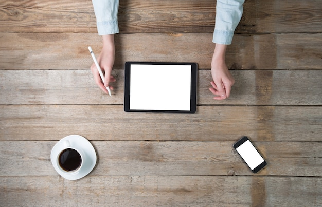 Kobieta za pomocą komputera typu tablet i telefonu na pulpicie z izolowanym ekranem. ogólny punkt widzenia. kobieta za pomocą rysika