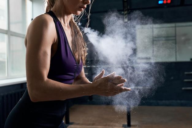 Kobieta za pomocą kredy przed intensywnym treningiem