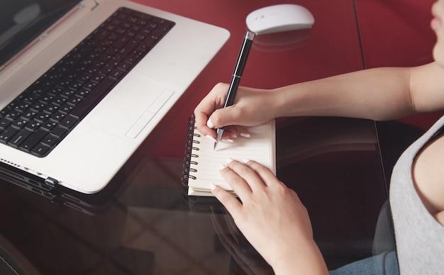 Kobieta za pomocą laptopa i pisania w notatniku.