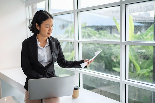 Kobieta za pomocą laptopa i trzymając papierkową robotę do sprawdzania budżetu w biurze.