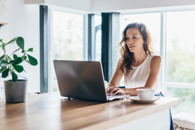 Kobieta za pomocą laptopa siedząc w domu.
