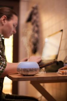 Kobieta za pomocą laptopa w domu podczas covid-19 i parownika do aromaterapii.