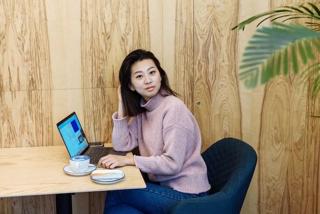 Kobieta za pomocą laptopa w kawiarni