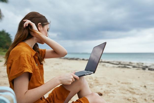Kobieta za pomocą laptopa w tropikalnej plaży z palmami