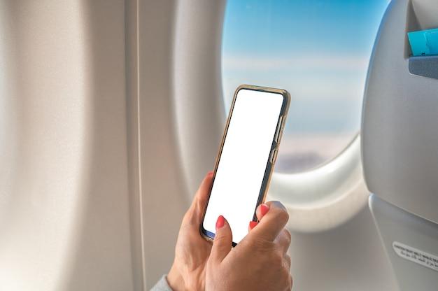 Kobieta za pomocą makiety telefonu komórkowego siedząc w samolocie kobieta za pomocą smartfona w locie samolotem.