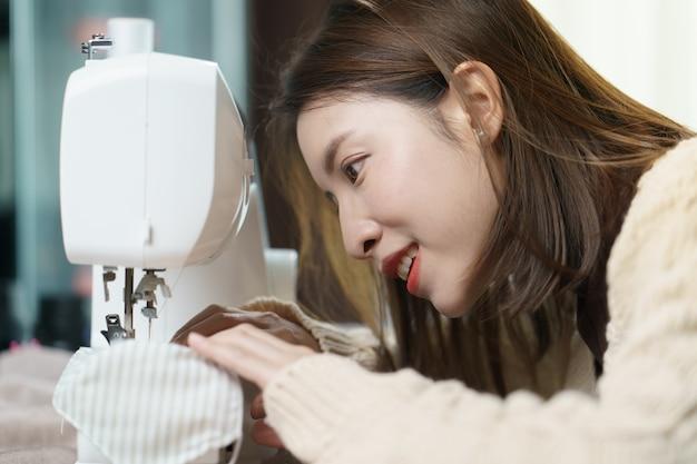 Kobieta za pomocą maszyny do szycia do szycia maski na twarz podczas pandemii koronawirusa.