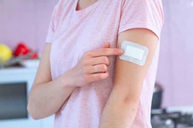 Kobieta za pomocą medycznego plastra bakteriobójczego na ramieniu po szczepieniu, szczepionce iniekcyjnej lub leku. pierwsza pomoc w przypadku skaleczeń i ran