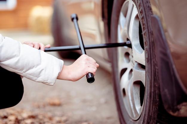 Kobieta za pomocą narzędzia na kole samochodu