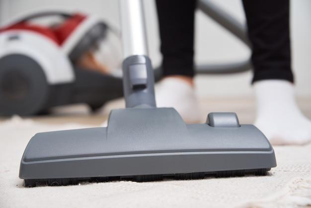 Kobieta za pomocą odkurzacza na podłodze