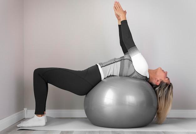 Kobieta za pomocą piłki fitness do ćwiczeń