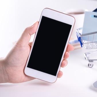 Kobieta za pomocą posiadania inteligentnego telefonu komórkowego zostaje w domu płatności elektronicznych online