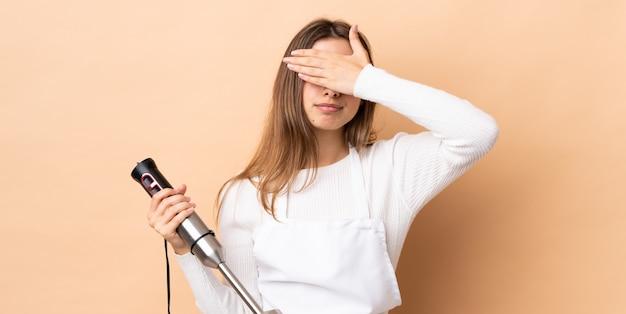 Kobieta za pomocą ręcznego blendera coning oczy rękami. nie chcę czegoś zobaczyć
