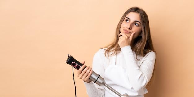 Kobieta za pomocą ręcznego blendera ma wątpliwości