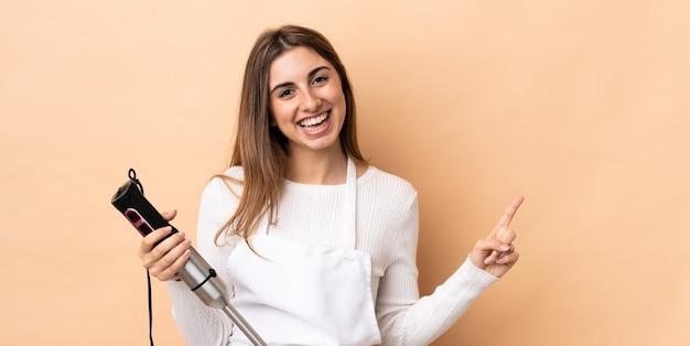 Kobieta za pomocą ręcznego miksera na odizolowanej ścianie wskazując palcem w bok i przedstawia produkt