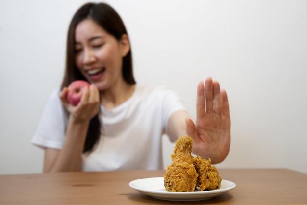 Kobieta za pomocą ręki odrzuca śmieciowe jedzenie, wypychając swój ulubiony smażony kurczak i wybiera czerwone jabłko i sałatkę dla dobrego zdrowia.