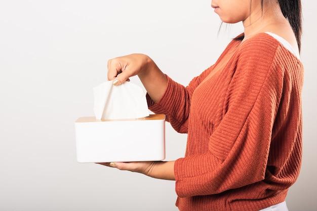 Kobieta za pomocą ręki wyciąga białą chusteczkę do twarzy z białego pudełka po czystą chusteczkę