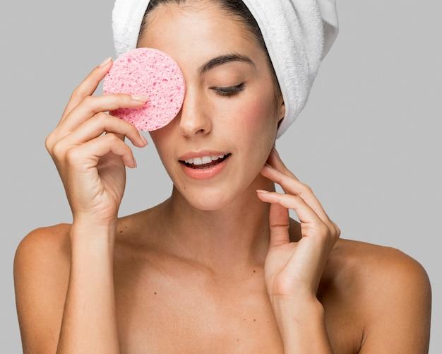 Kobieta za pomocą różowej gąbki i patrząc w dół