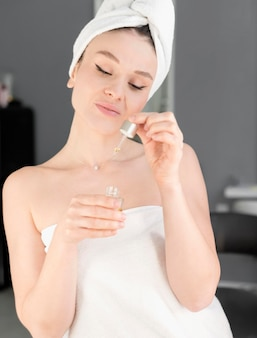 Kobieta za pomocą serum do twarzy