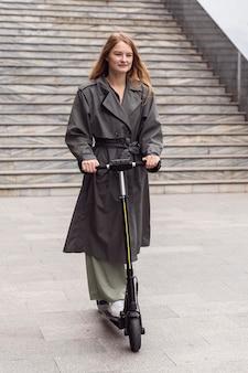 Kobieta za pomocą skutera elektrycznego na zewnątrz