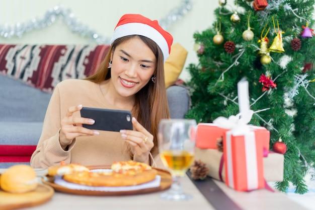 Kobieta za pomocą smartfona do zrobienia zdjęcia obiadu na święta bożego narodzenia i koncepcji uroczystości