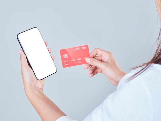 Kobieta za pomocą smartfona i karty kredytowej do zakupów online, płatności lub czeków na koncie bankowym.