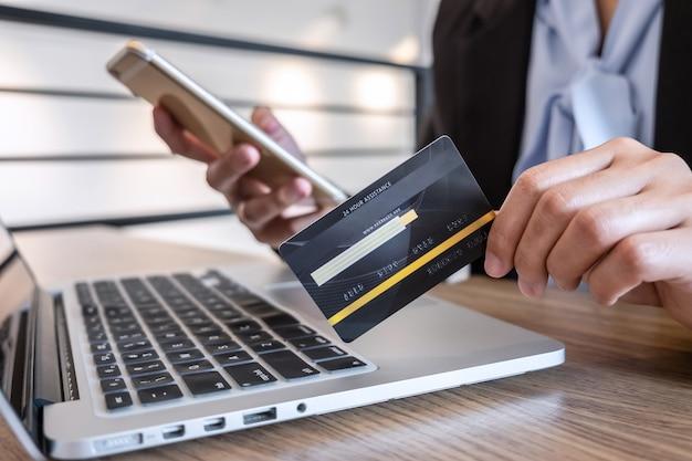 Kobieta za pomocą smartfona, laptopa i posiadania karty kredytowej