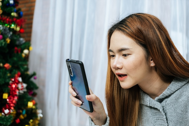 Kobieta za pomocą smartfona na łóżku w zimny dzień