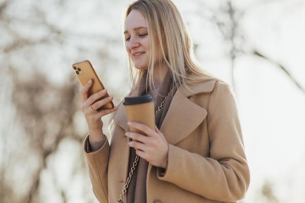 Kobieta za pomocą smartfona podczas picia kawy w mieście