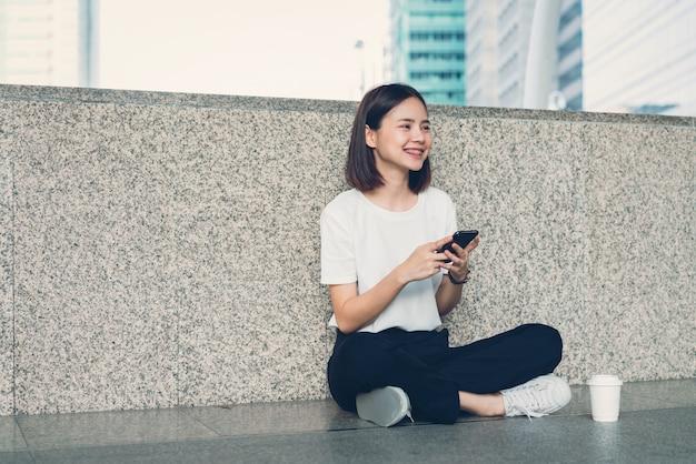 Kobieta za pomocą smartfona, w czasie wolnym. koncepcja korzystania z telefonu jest niezbędna w życiu codziennym.