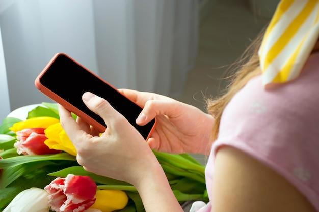 Kobieta za pomocą smartfona w ręce z kwiatami na kolanach