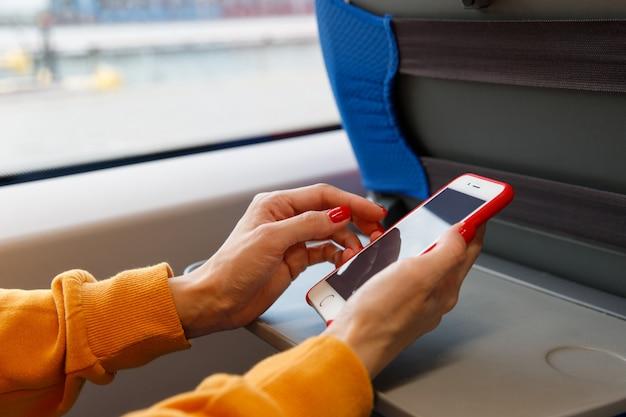 Kobieta za pomocą smartfona w transporcie publicznym