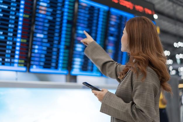 Kobieta za pomocą smartfona z tablicą informacyjną lotu na lotnisku