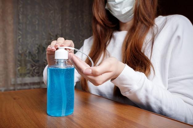 Kobieta za pomocą środka dezynfekującego do rąk